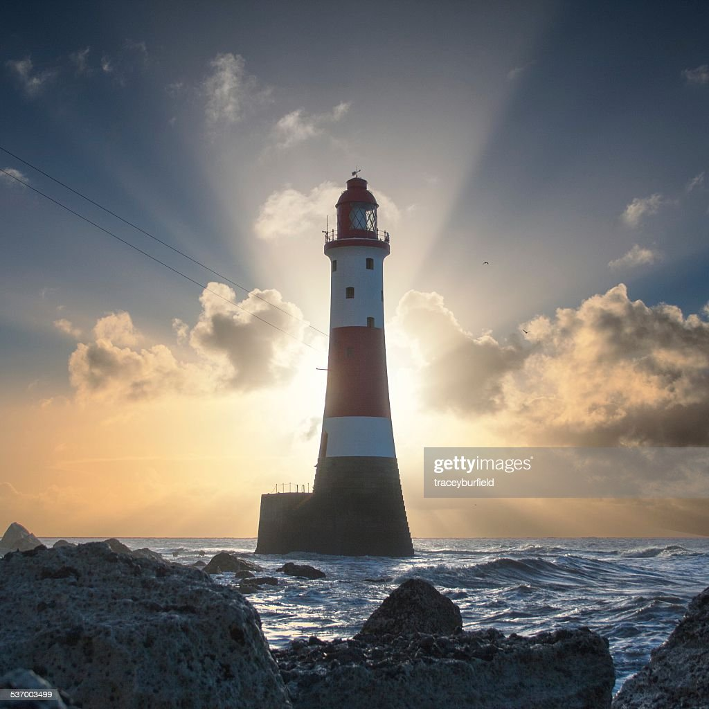 United Kingdom, England, East Sussex, Beachy Head, Beachy Head Lighthouse backlit by rising sun : Stock Photo