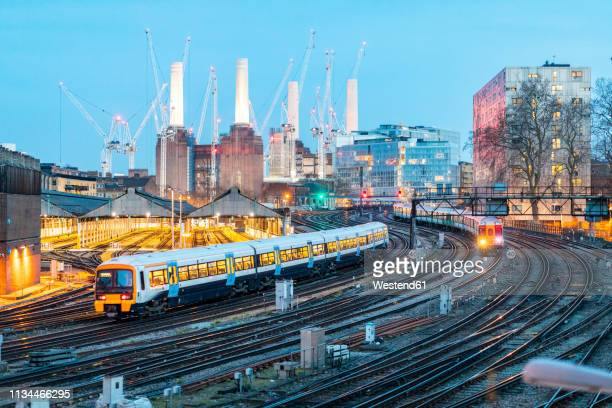 united kingdom, england, london, view of railtracks and trains in the evening, former battersea power station and cranes in the background - greater london stock pictures, royalty-free photos & images
