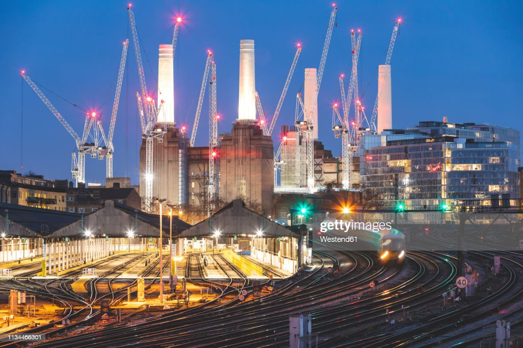 United Kingdom, England, London, view of railtracks and trains in the evening, former Battersea Power Station and cranes in the background : ストックフォト