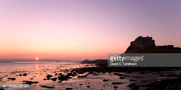 united kingdom, england, northumberland, holy island, silhouette of lindisfarne castle at sunset - 2007 stock pictures, royalty-free photos & images