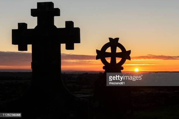 united kingdom, england, old sodbury, church of saint john the baptist, grave yard, crosses at sunset - grab stock-fotos und bilder