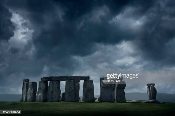 united kingdom, england, storm clouds above stonehenge - stone material stock pictures, royalty-free photos & images