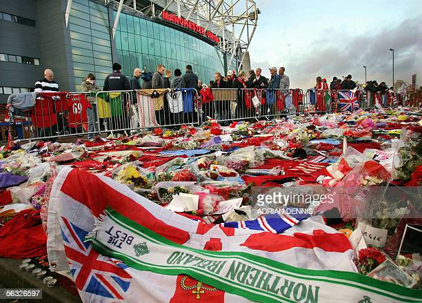 Football fans looks at shirts scarves and flowers left as tributes to exfootballer George Best outside Manchester United's stadium at Old Trafford in...