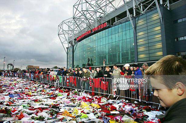 Football fans queue past shirts scarves and flowers left as tributes to exfootballer George Best outside Manchester United's stadium at Old Trafford...