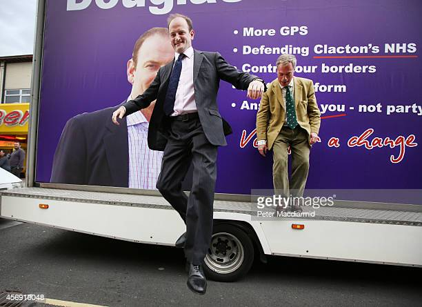 United Kingdom Independence Party candidate Douglas Carswell jumps from a mobile poster truck with party leader Nigel Farage on polling day on...