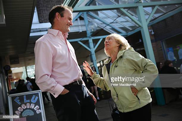 United Kingdom Independence Party candidate Douglas Carswell talks with supporter Asma Jackson as he canvasses for votes on October 8 2014 in...
