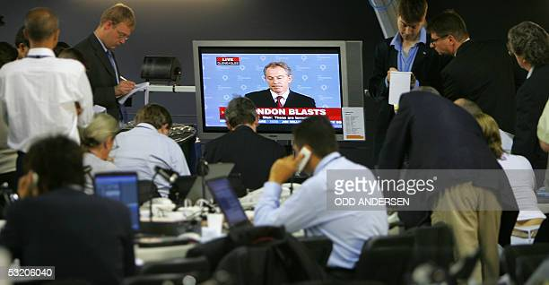 Journalists covering the G8 summit at Gleneagles hotel gather around a TV set to hear British Prime minister Tony Blair give a statement on a series...