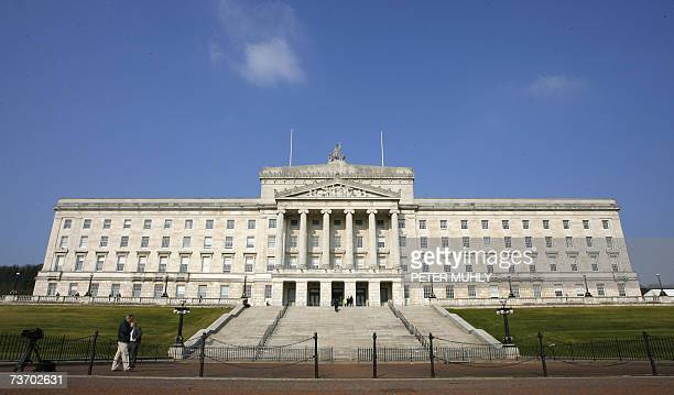 People walk past the Stormont Assembly building in Belfast Northern Ireland 26 March 2007 An accord between Northern Ireland's main party leaders to...