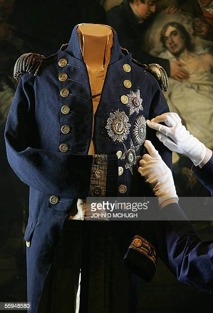 United Kingdom: Photo taken 01 July 2005 of a curator adjusting the uniform of Horatio Nelson in the National Maritime Museum in London in front of...