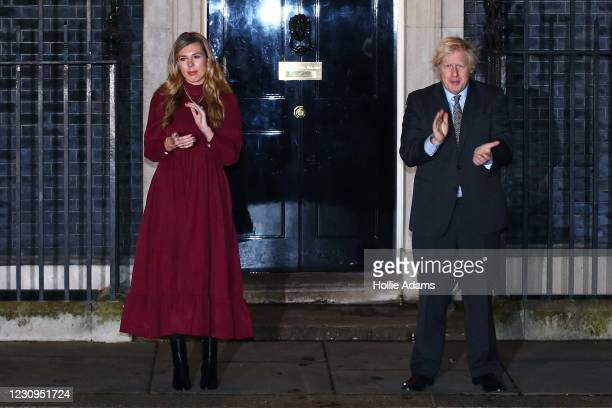 United Kingdom prime minister Boris Johnson and his fiancee Carrie Symonds take part in a doorstep clap in memory of Captain Sir Tom Moore outside 10...