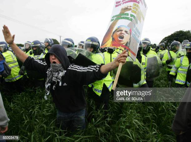United Kingdom: Riot police officers force anti-G8 protestors away, outside the perimeter fences of Gleneagles hotel where the G8 summit is taking...