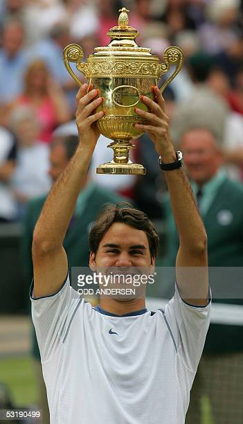 Roger Federer of Switzerland holds the trophy after defeating Andy Roddick of US after their men's final match at the 119th Wimbledon Tennis...