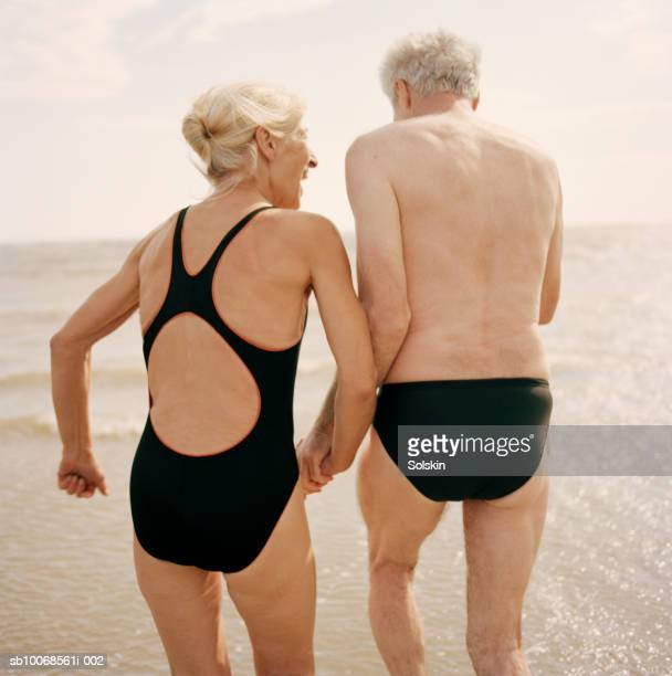 United Kingdom, Rye, Camber Sands, couple holding hands at ocean