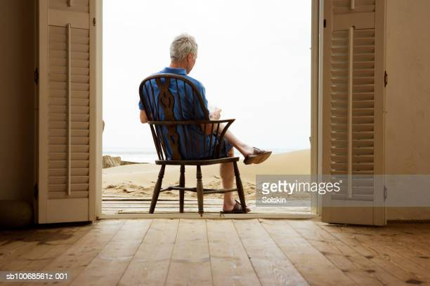 United Kingdom, Rye, Camber Sands, man reading in beach house doorway