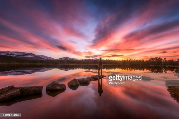 united kingdom, scotland, highlands, cairngorms national park, loch morlich, sunset, hiker standing on stone - sunset stock pictures, royalty-free photos & images