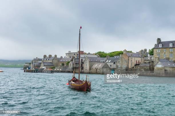 united kingdom, scotland, shetland islands, mainland, old viking boat before the seafront of lerwick - isole shetland foto e immagini stock