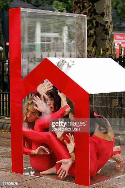 Three contortionists squeeze into a small perspex house in Leicester Square in central London 24 August in a protest organised by the charity...