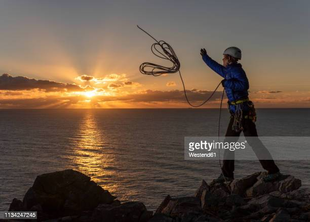 united kingdom, wales, pembrokeshire, st govan's, female climber throwing rope - govan stock pictures, royalty-free photos & images