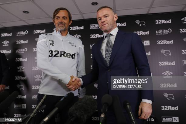 DC United midfielder and former England captain Wayne Rooney and Derby County's Dutch manager Phillip Cocu shake hands during a press conference at...