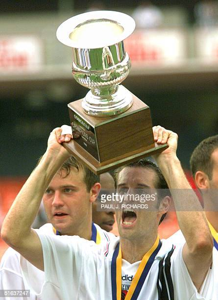 United midfielder John Harkes holds the 1998 CONCACAF Champions Cup trophy after DC United defeated CD Toluca 1-0 16 August in the final of the...