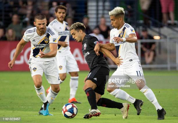 C United midfielder Lucas Rodriguez cuts away from Los Angeles Galaxy defender Perry Kitchen and forward Favio Alvarez during a MLS match between DC...