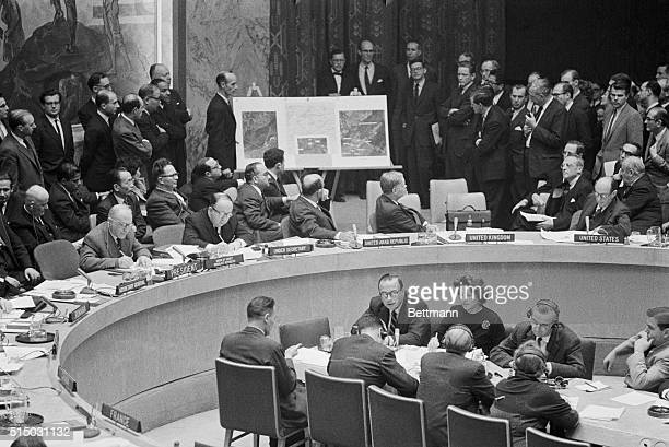 US United Nations ambassador Adlai Stevenson and Soviet ambassador Valerian Zorin turn to look at display of aerial photos brought into the Security...