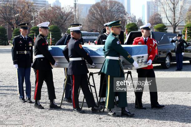 United Nations Command honour guards carry a coffin which contains the remains of a soldier who fought in the Korean War during a repatriation...