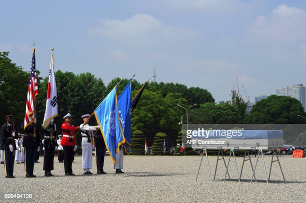 United Nations Command honour guards hold flags in front of a coffin containing the remains of an unidentified Korean War UN forces soldier during a...