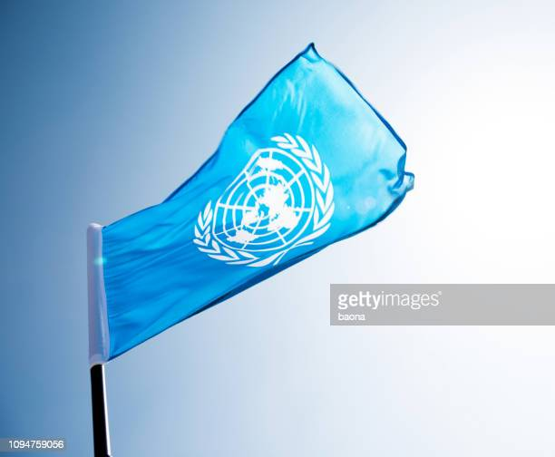 united nations flag waving in the wind - peacekeeping stock pictures, royalty-free photos & images