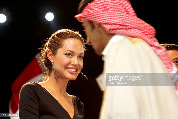 United Nations goodwill ambassador actress Angelina Jolie shakes hands with a participant during the 24th Arab Children Congress July 21 2004 in...