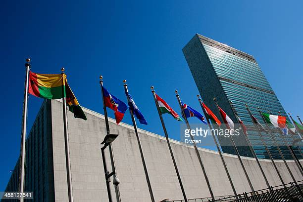 united nations headquarters with waving flags in new york, usa - united nations building stock pictures, royalty-free photos & images