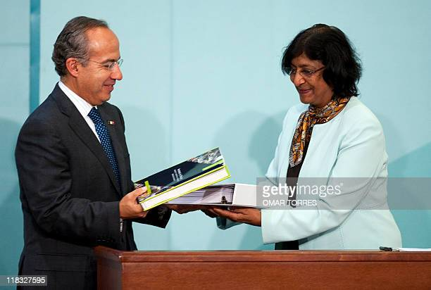 United Nations High Commissioner for Human Rights Navy Pillay and Mexican President Felipe Calderon exchange reports during the meeting called...