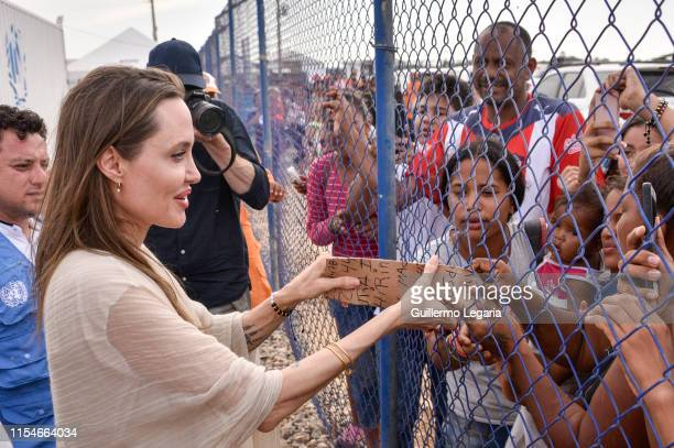 United Nations High Commissioner for Refugees Special Envoy Angelina Jolie greets people during her visit to a refugee camp in the border between...