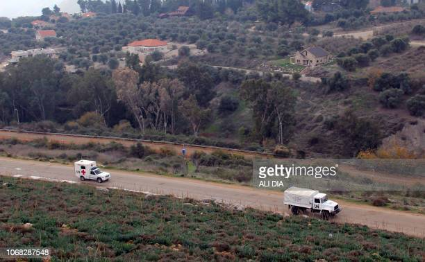 United Nations Interim Forces in Lebanon vehicles are seen driving on a road near the border between the southern Lebanese village of Kfar Kila and...