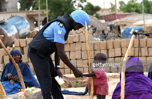 A United Nations MUNISMA peacekeeper speaks to a child while on patrol through the streets Gao eastern Mali on August 3 2018 President Ibrahim...