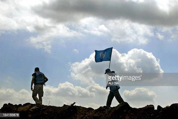 United Nations observers walk on a sand barrier to monitor the situation in the southern village of Ghajar, part of which is in Lebanon and another...