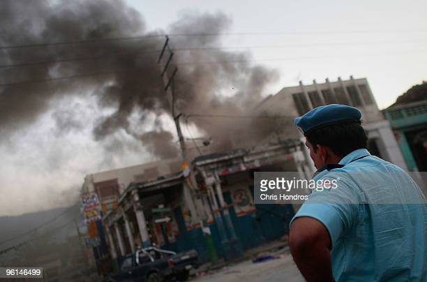 United Nations peacekeeper from India stands near a burning building in the ruins of downtown January 24, 2010 in Port-au-Prince, Haiti. Central...