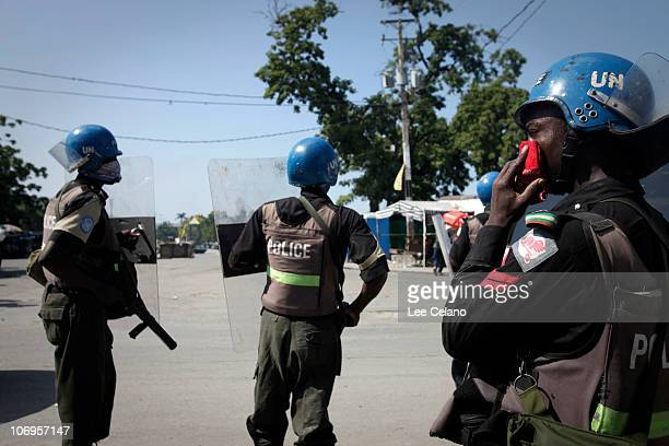 United Nations peacekeeper from Nigeria places a handerchief onto his mouth after tear gas was fired on protestors amid growing tensions between...