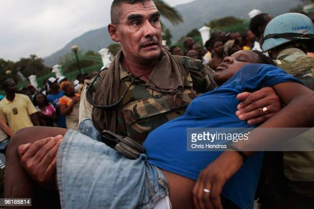 United Nations peacekeeper from Uruguay carries a pregnant Haitian woman who lost consciousness in a massive crowd during a rice distribution for...