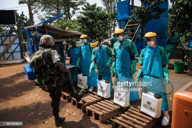 A United Nations peacekeeper has his shoes cleaned with a chlorine solution before leaving an Ebola treatment centre in Mangina North Kivu province...