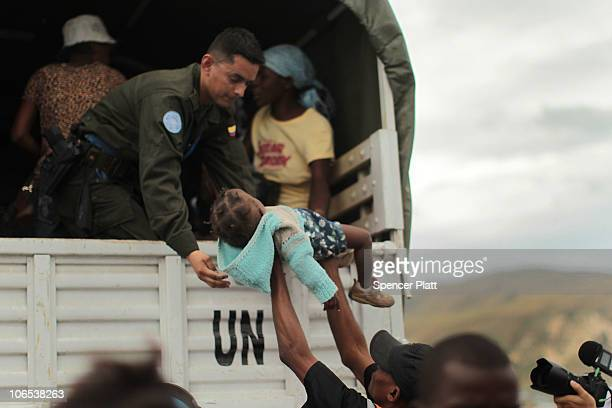United Nations peacekeeper is handed a child during the evacuation of over 1000 of the most vulnerable residents of the CorailCesselesse relocation...