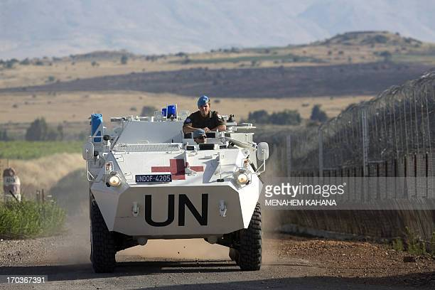 A United Nations peacekeeper vehicle make its way along the Israeli border with Syria next to the crossing of Quneitra between Syria to the Israeli...