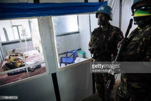 United Nations peacekeepers stand next to a patient during a visit of the UN secretarygeneral at an Ebola treatment centre in Mangina North Kivu...
