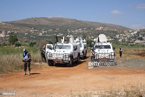 United Nations peacekeepers stand next to their armored vehicles on the Lebanese side of the border with Israel opposite the northern Israeli village...