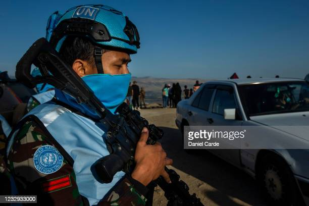 United Nations peacekeeping force in Lebanon soldier monitors a demonstration to show solidarity with Palestinians as near the Lebanon-Israel border...