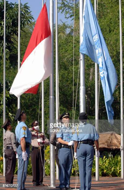 United Nations policemen and Indonesian policemen hoist Indonesian and an UN flags before the inauguration of a conference on 'waste management for...
