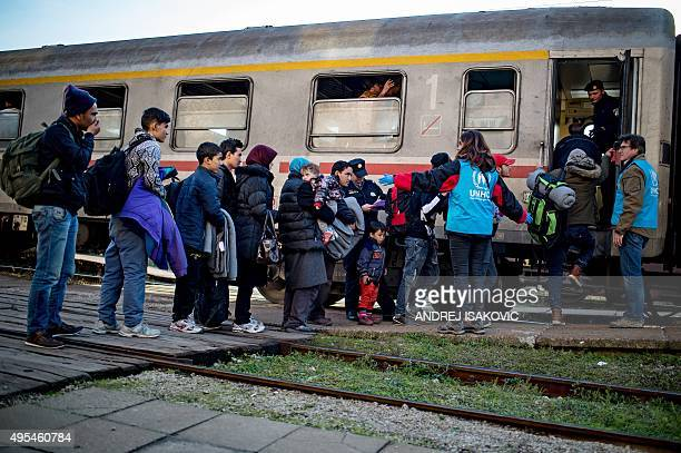 United Nation's Refugee Agency workers assist migrants and refugees board a train at the railway station in the western Serbian town of Sid on...
