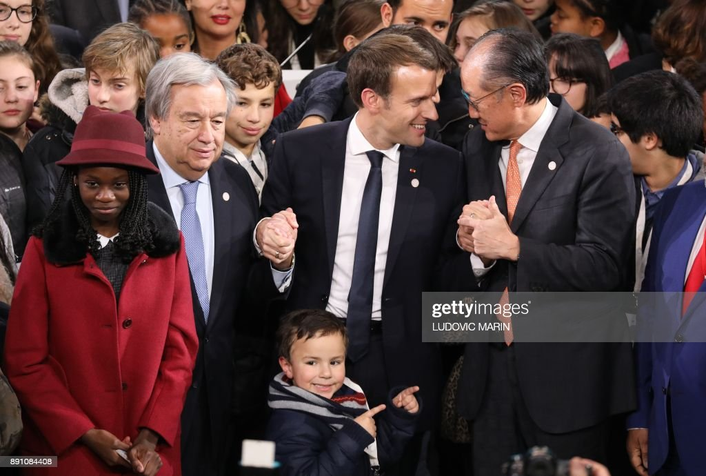United Nations (UN) Secretary General Antonio Guterres (L), French President Emmanuel Macron (C) and World Bank President Jim Yong Kim (R) pose at the end of a session of the One Planet Summit on December 12, 2017, at La Seine Musicale venue on l'ile Seguin in Boulogne-Billancourt, southwest of Paris. ?The French President hosts 50 world leaders for the 'One Planet Summit', hoping to jump-start the transition to a greener economy two years after the historic Paris agreement to limit climate change. /