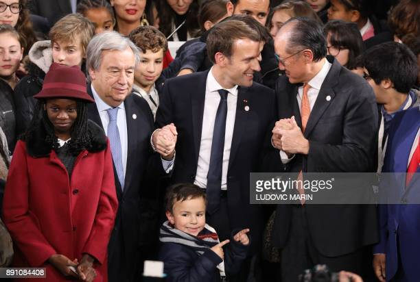 United Nations Secretary General Antonio Guterres French President Emmanuel Macron and World Bank President Jim Yong Kim pose at the end of a session...
