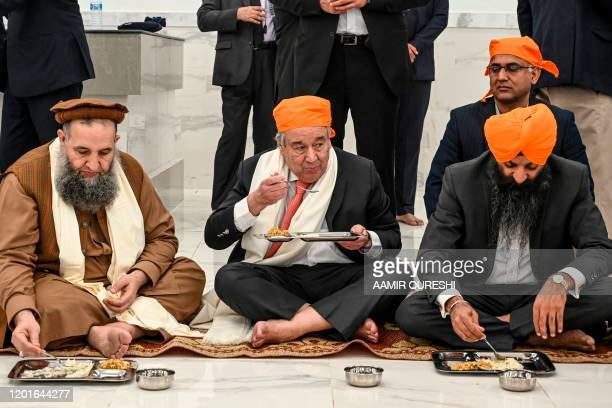 United Nations SecretaryGeneral Antonio Guterres eats food along with Pakistan's Religious Affairs Minister NoorulHaq Qadri during his visit of the...